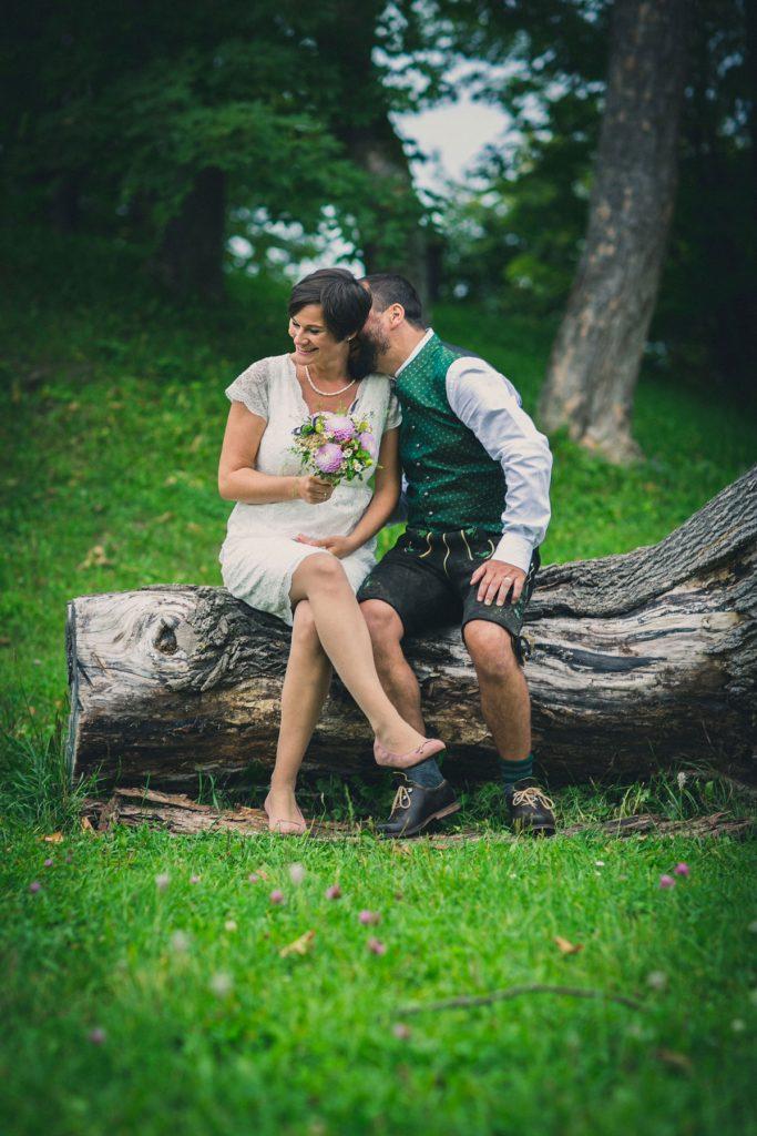 Hochzeitspaar auf einem Baumstamm