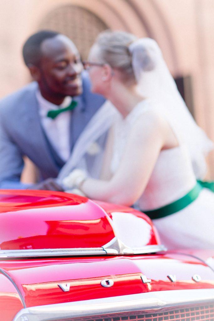 Farbiges Hochzeitspaar am Hochzeitsauto