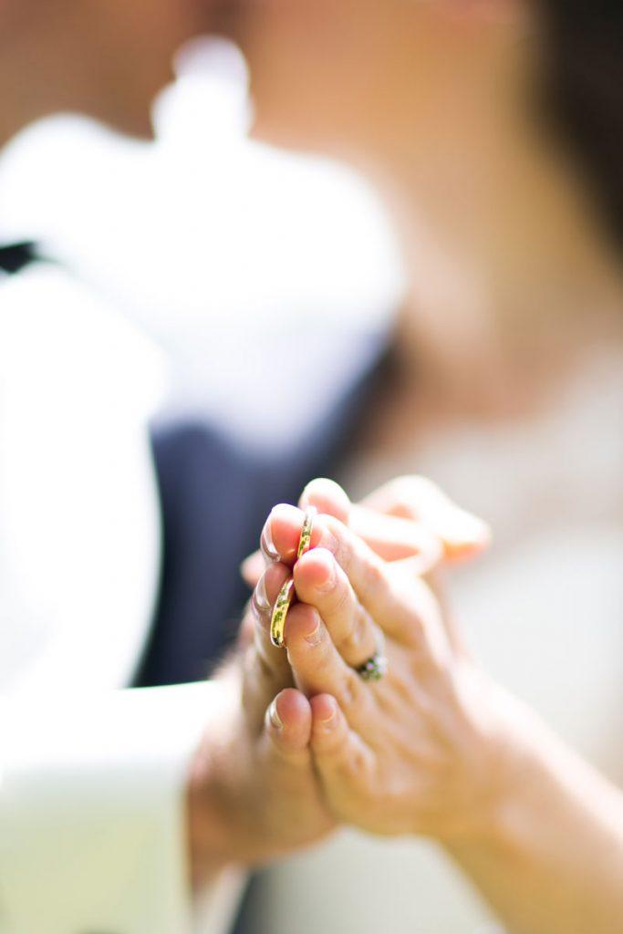 Eheringe in den Händen des Hochzeitspaares
