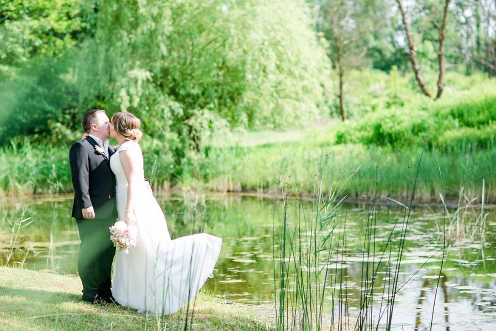 Hochzeitspaar beim Küssen am See