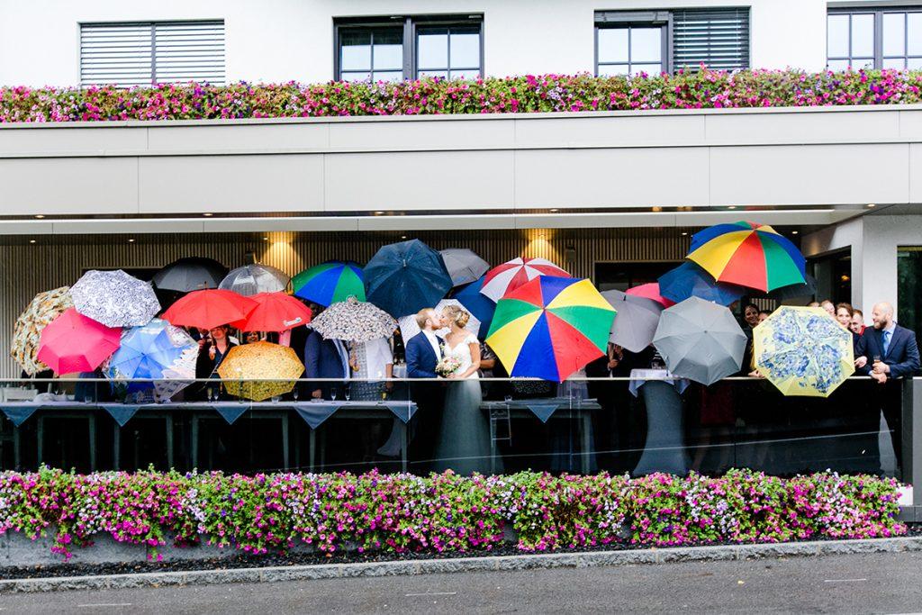 Brautpaar mit Regenschirmen bei Regenhochzeit