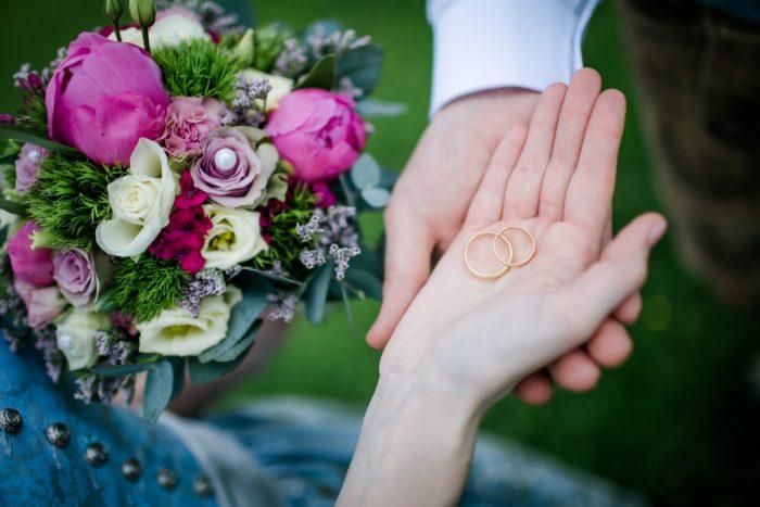 Hochzeitsringe in der Hand